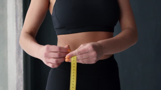 Fitness Woman With Tape Measure Showing Her Waist