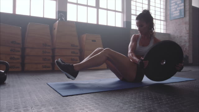 Fitness woman working out on core muscles at gym