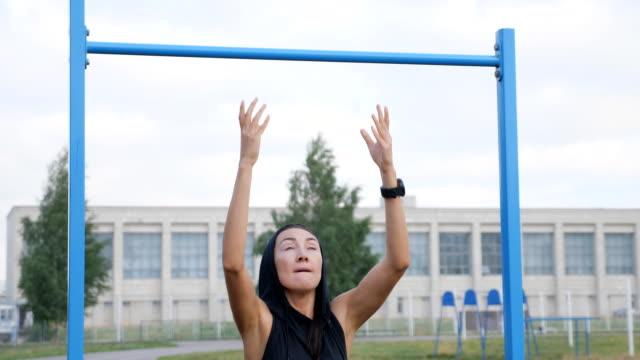 fitness-frau-workout übungen auf einer horizontalen bar im freien. - turngerät mit holm stock-videos und b-roll-filmmaterial