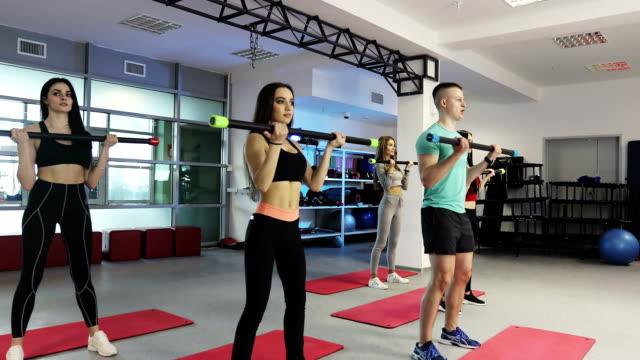 フィットネス女性は、ジムで体バーとトレーニングです。 - 有酸素運動点の映像素材/bロール