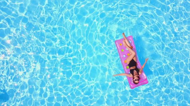 vídeos de stock, filmes e b-roll de uma garota bonita de biquíni resfriando um colchão rosa inflável na piscina. mulher em forma de bronzeamento de maiô. mulher relaxando em flutuar em água azul em resort de luxo. antena, vista de cima - flutuando na água