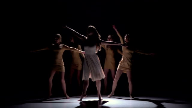 Five beautiful girls start dancing modern contemporary dance, on black, shadow, slow motion video