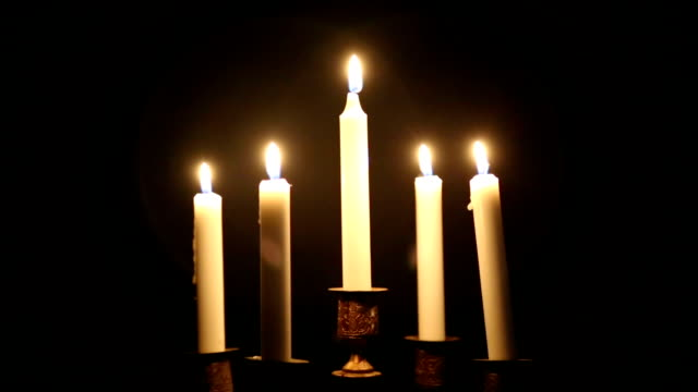 five burning candles in a candlestick. - candeliere video stock e b–roll