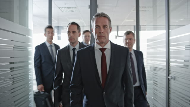 Five businessmen walking down the hall and into the office for a meeting Wide handheld shot of a team of five businessmen walking down the office hallway and into the meeting room. Shot in Slovenia. board room stock videos & royalty-free footage