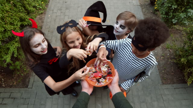 Five Children Taking Candies from Bowl on Halloween