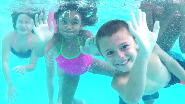 Five children underwater swimming toward camera A group of five multi-ethnic children on the lazy river at a water park, swim underwater toward the camera, waving and smiling. swimming stock videos & royalty-free footage