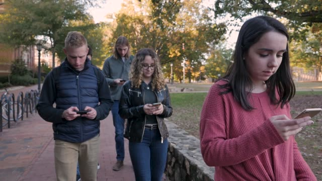 Five college students walking and looking down at their mobile phones on campus
