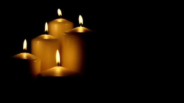 Five flickering candles on the black background video