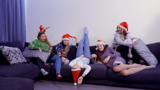5 人の女の子は、クリスマスの前夜、自宅のソファーで楽しい時を過す - サンタの帽子点の映像素材/bロール