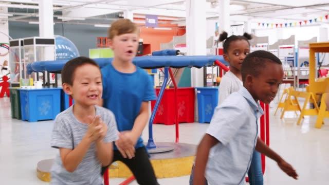 vidéos et rushes de cinq enfants dansant autour et s'amuser dans un centre de sciences - école primaire