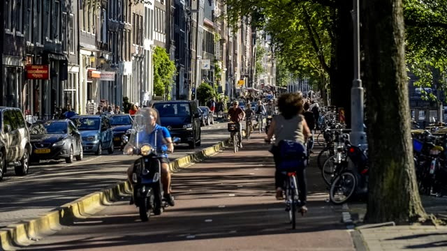 Five o'clock rush hour in Amsterdam, Gelderse kade. Commuters on bicycles riding back home after a work Five o'clock rush hour in Amsterdam, Gelderse kade. amsterdam stock videos & royalty-free footage