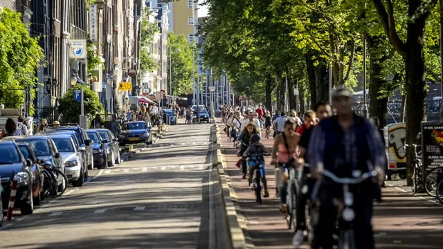 five o'clock rush hour in amsterdam, gelderse kade. commuters on bicycles riding back home after a work - veicolo a due ruote video stock e b–roll