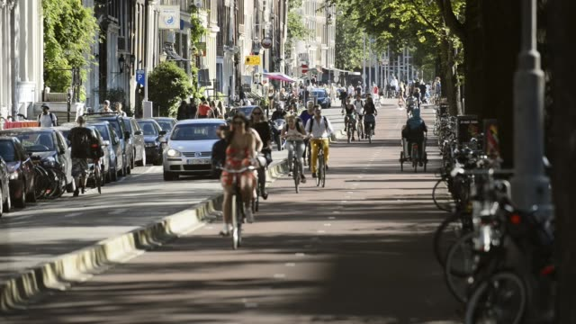 Five o'clock rush hour in Amsterdam, Gelderse kade. Five o'clock rush hour in Amsterdam, Gelderse kade. Summer time Commuters on bicycles riding back home after a work netherlands stock videos & royalty-free footage