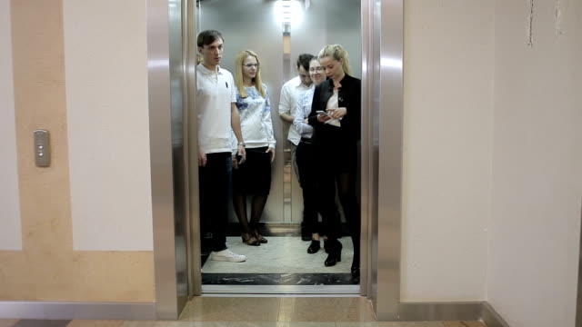 five workers in the elevator - ascensore video stock e b–roll