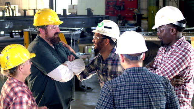 Five workers meeting on factory floor, laughing A multi-ethnic group of five workers wearing hard hats and safety glasses in a meeting. The supervisor talking to his crew is a mid adult African-American man in his 30s. There is one woman in the group of men. They are laughing. work helmet stock videos & royalty-free footage
