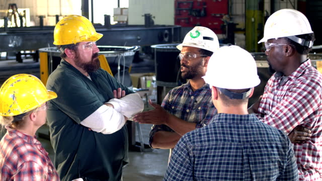 Five workers meeting on factory floor A multi-ethnic group of five workers wearing hard hats and safety glasses in a meeting. The supervisor talking to his crew is a mid adult African-American man in his 30s. There is one woman in the group of men. manual worker stock videos & royalty-free footage