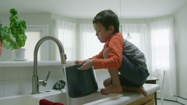A Five Year-Old Caucasian Boy Opens a Cabinet, Pulls out a Tall Pot, Climbs on to the Counter, and Starts Filling the Pot with Water from the Kitchen Sink