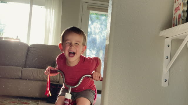 A Five Year-Old Caucasian Boy Surprises His Three Year-Old Caucasian Brother Riding a Tricycle Who Then Laughs as the Two Boys Play with Each Other Indoors in a House