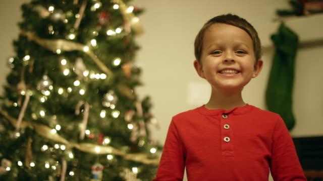ein fünf-jährige kaukasische junge mit einem roten hemd lächelt und lacht vor einem weihnachtsbaum - weihnachtsstrumpf stock-videos und b-roll-filmmaterial