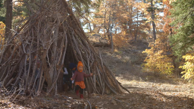 five young children playing together leave a hut in a forest - capanna video stock e b–roll