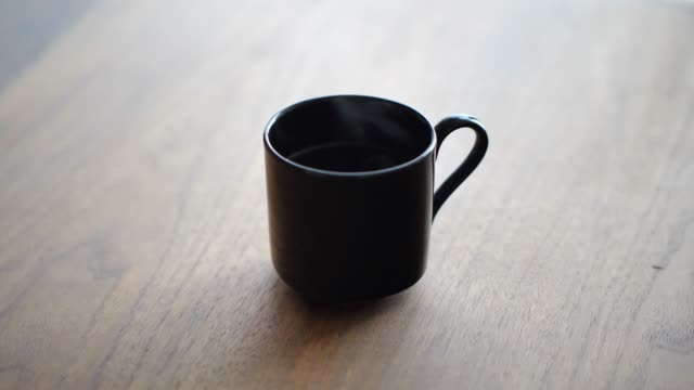 Fixed view of a black ceramic or porcelain coffee mug or tea cup with hot liquid that is steaming as it sits on a walnut wood table with natural light coming from a nearby window. Fixed view of a black ceramic or porcelain coffee mug or tea cup with hot liquid that is steaming as it sits on a walnut wood table with natural light coming from a nearby window. mug stock videos & royalty-free footage