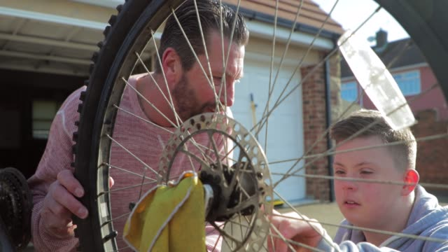 Fixing a Bike at Home A boy with down syndrome fixes a bike on the driveway whilst his father tickles him. disability stock videos & royalty-free footage