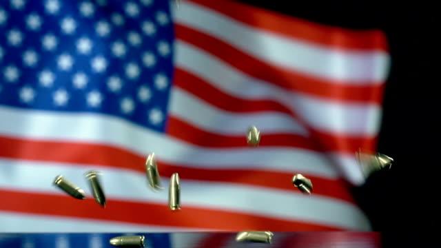 vidéos et rushes de indicateur des usa derrière des balles tombant dans le mouvement lent - armement