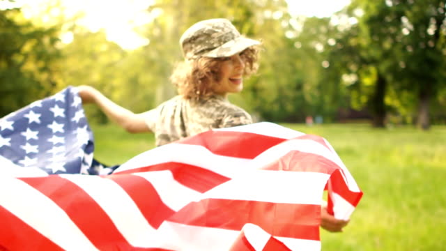 USA flag is held by a running guy in camouflage on the background of a summer park and sky Outdoor Patriotic day
