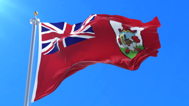 Flag of Bermuda waving at wind in slow with blue sky, loop video