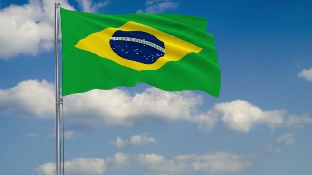 Bandeira do Brasil, contra o fundo de nuvens flutuando no céu azul - vídeo