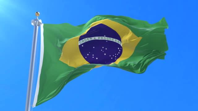 flagga brasilien viftande på vinden i långsamt med blå himmel, slinga - brasilien flagga bildbanksvideor och videomaterial från bakom kulisserna