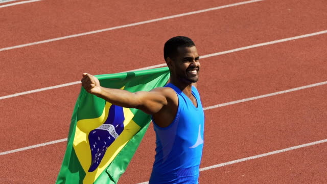 flag of brazil waving in wind, athlete showing his strength, winning competition - спортсмен стоковые видео и кадры b-roll