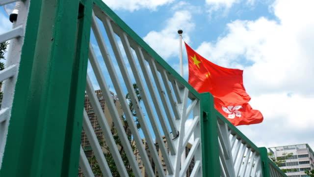 Bandera de China y Hong Kong ondeando en el viento con cielo azul - vídeo