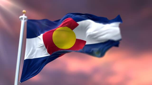 vidéos et rushes de drapeau de l'état du colorado, région des états-unis, agitant au coucher du soleil-boucle - alaska état américain