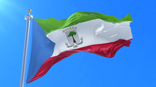 Flag of Equatorial Guinea waving at wind with blue sky in slow, loop video