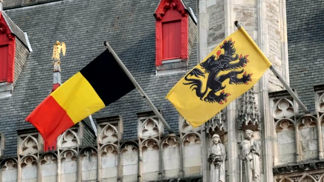 flag of flanders and belgium flag on old building - bruges video stock e b–roll