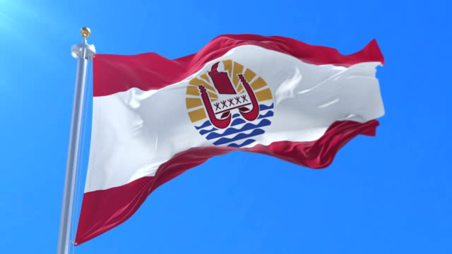 Flag of French Polynesia waving at wind with blue sky in slow, loop video