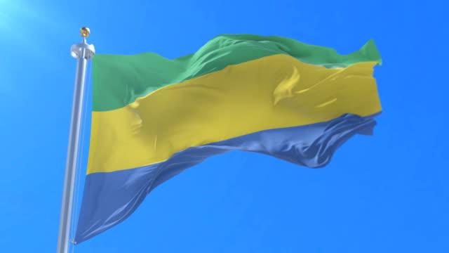 Flag of Gabon waving at wind with blue sky in slow, loop video
