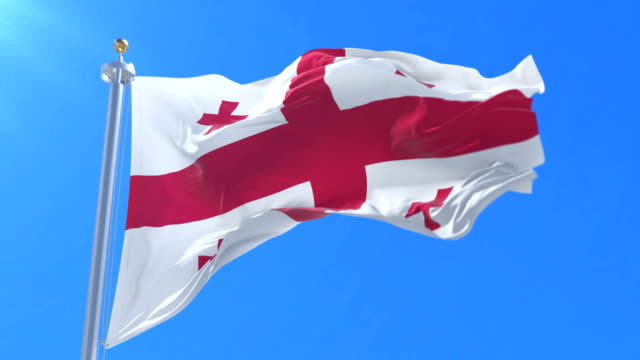 Flag of Georgia waving at wind in slow in blue sky, loop video
