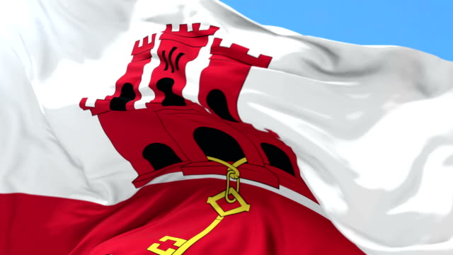 Flag of Gibraltar waving at wind with blue sky, loop video