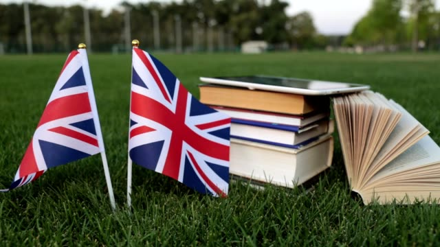 flag of great britain and books on the grass. education in england, english. - english video stock e b–roll