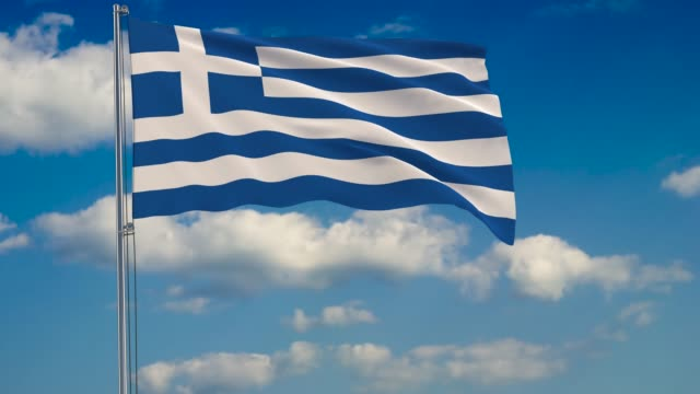 flag of greece against background of clouds floating on the blue sky - grecia stato video stock e b–roll