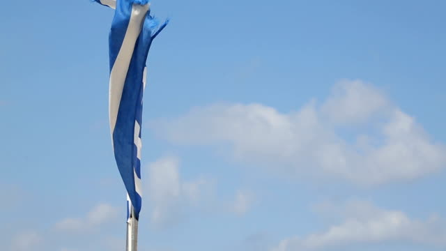 flag of greece swaying in strong wind against white clouds in blue sky, summer - grecia stato video stock e b–roll
