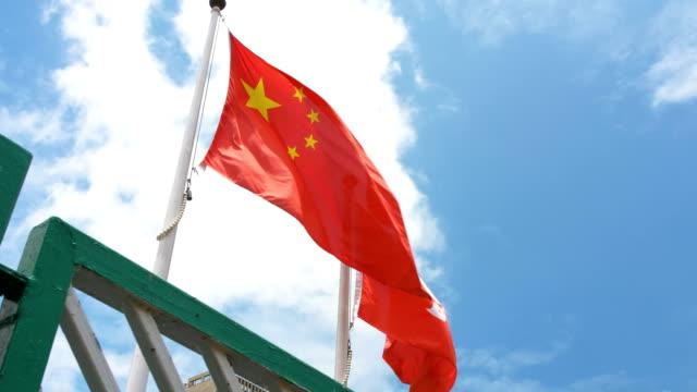 Bandera de Hong Kong y China ondeando en el viento con cielo azul - vídeo