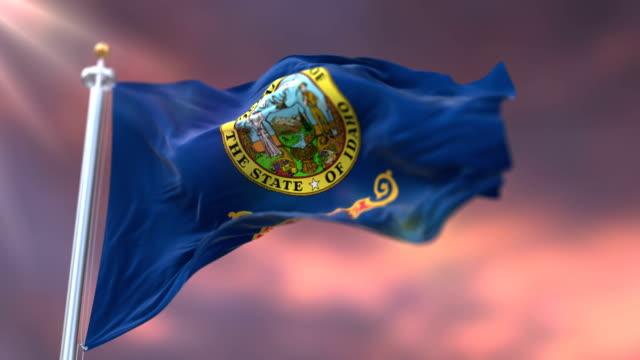 vidéos et rushes de drapeau de l'état de l'idaho au coucher du soleil, région du nord-ouest des états-unis-boucle - alaska état américain