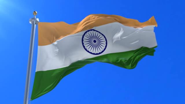 Flag of India waving at wind in slow in blue sky, loop video