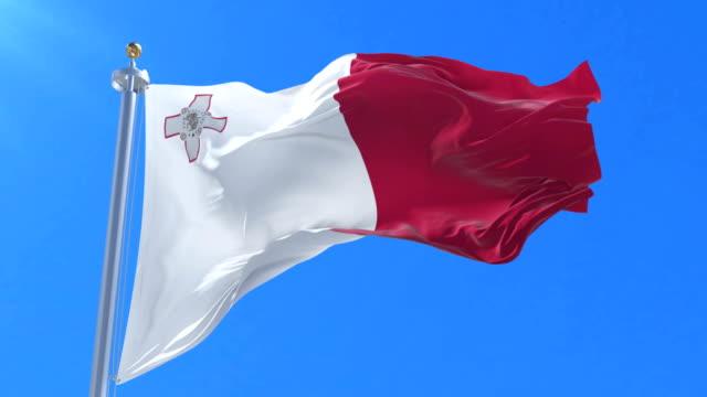 Flag of Malta waving at wind with blue sky in slow, loop video