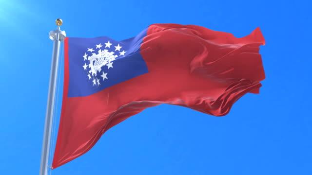 flag of myanmar or union of burma waving at wind in slow in blue sky, loop - naypyidaw video stock e b–roll