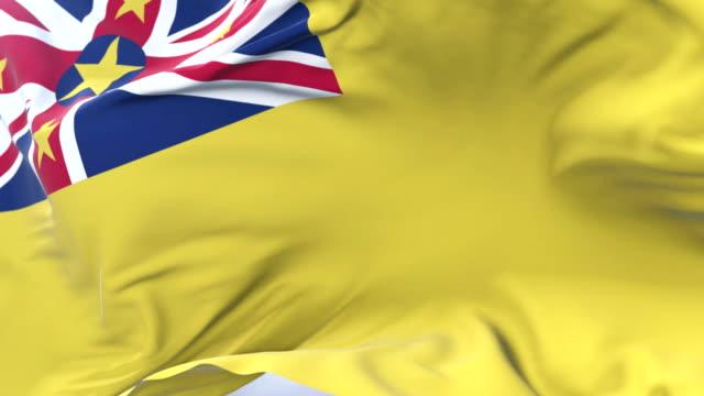 Flag of Niue waving at wind in slow in blue sky, loop video