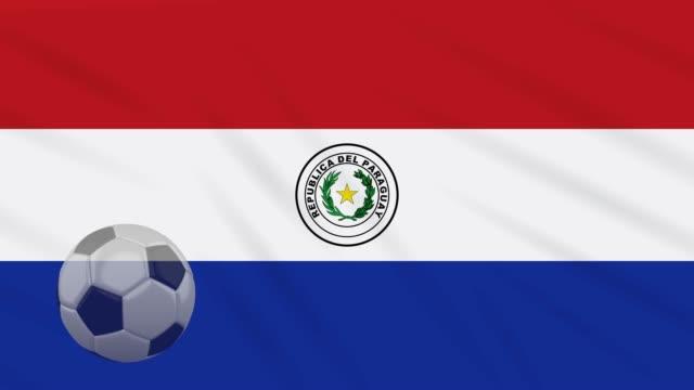 флаг парагвая и футбольный мяч вращаются на фоне размахивая тканью - парагвай стоковые видео и кадры b-roll
